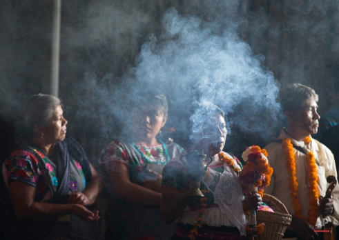 A woman wearing traditional indigenous dress carries incense as a procession enters the Basilica of Guadalupe in Mexico City, Tuesday, Oct. 13, 2015. The Basilica celebrated its first ever Mass in the indigenous language of Nahuatl on Tuesday. (AP Photo/Rebecca Blackwell)