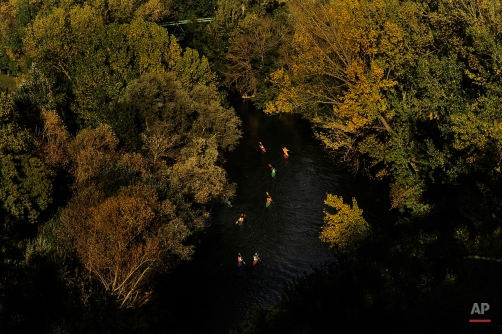A group of paddlers makes their way along the Arga River as the sun sets on a Autumn day, in Pamplona, northern Spain, Tuesday, Oct. 13 2015. As the temperature drifts towards winter it is still warm enough to attract people into the open air for a little exercise. (AP Photo / Alvaro Barrientos)