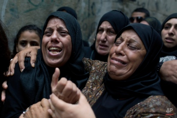 """Palestinian Dalal Abeidallah, left, mother of 13 year old, Abdel Rahman Shadi, who died after being hit by a live bullet to the chest after throwing a stone at Israeli army soldiers, cries while being comforted by mourning relatives during her son's funeral procession, at Aida Refugee camp, in the West Bank city of Bethlehem, Tuesday, Oct. 6, 2015. Israeli Prime Minister Benjamin Netanyahu warned Monday that he will use a """"strong hand"""" to quell violent Palestinian protests and deadly attacks, signaling that the current round of violence is bound to escalate at a time when a political solution to the conflict is increasingly distant. (AP Photo/Nasser Nasser)"""