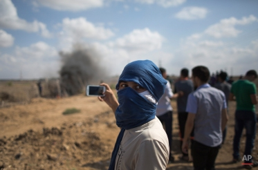 A Palestinian protester films with his mobile phone, during clashes with Israeli soldiers on the Israeli border Eastern Gaza City, Friday, Oct. 9, 2015. At least four attacks ó three by Palestinians and one by an Israeli ó as well as deadly clashes along the Gaza border threatened to escalate tensions throughout the country on Friday as Israel struggled to control spiraling violence. (AP Photo/Khalil Hamra)