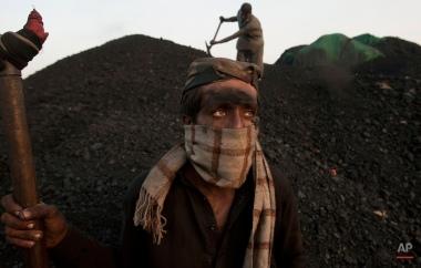 Pakistan's Waseem Akram takes a break while working at coal depot in Karachi, Pakistan, Tuesday, Oct. 6, 2015. (AP Photo/Shakil Adil)