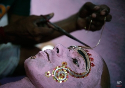 An Indian man applies make up on an artist as he prepares for a procession on the first day of the nine-day Navratri festival in Allahabad, India, Tuesday, Oct. 13, 2015. Feasting and fasting takes over normal life for millions of Hindus during Navratri, the festival of nine nights. (AP Photo/Rajesh Kumar Singh)