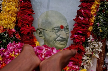 An Indian boy pays tribute to a portrait of Mahatma Gandhi on the occasion of his birth anniversary, in Hyderabad, India, Friday, Oct. 2, 2015. (AP Photo/Mahesh Kumar A.)