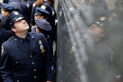 A police officer looks at the names of officers who died in the line of duty during a rededication ceremony at the Police Memorial Wall in Battery Park, Tuesday, Oct. 13, 2015, in New York. Every year the New York Police Department holds a ceremony to honor officers who died in the line of duty in the past year. (AP Photo/Mary Altaffer)