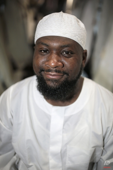 """In this Friday, Sept. 25, 2015 photo, Suleimaan Hamed, 35, CEO of Hajj Pros and Imam of Atlanta Masjid, poses for a picture outside his tent in Mina, outside the holy city of Mecca, Saudi Arabia. """"Pack your patience, and wear it,"""" Hamed always tells the Americans he guides on hajj. Patience is key to dealing with the hajj crowds. Another piece of advice: """"Take off your American glasses."""" (AP Photo/Mosa'ab Elshamy)"""