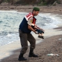 In this Sept. 2, 2015 photo, a paramilitary police officer carries the lifeless body of Aylan Kurdi, 3, after a number of migrants died and others were reported missing when boats carrying them to the Greek island of Kos capsized near the Turkish resort of Bodrum. The family Abdullah, his wife Rehan and their two boys, 3-year-old Aylan and 5-year-old Ghalib embarked on the perilous boat journey only after their bid to move to Canada was rejected. The tides also washed up the bodies of Rehan and Ghalib on Turkey's Bodrum peninsula Wednesday. Abdullah survived the tragedy. (AP Photo/DHA)