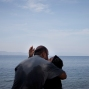 In this Wednesday, Sept. 9, 2015 photo, a woman and a man kiss as they arrive with others migrants from Turkey to Lesbos island, Greece, on a dinghy. (AP Photo/Petros Giannakouris)