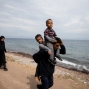An Afghan man carries his two sons in front of his pregnant wife after they arrived with other migrants from Turkey to the shores of the Greek island of Lesbos, Tuesday, Sept. 22, 2015. More than 260,000 asylum-seekers have arrived in Greece so far this year, most reaching the country's eastern islands on flimsy rafts or boats from the nearby Turkish coast. (AP Photo/Petros Giannakouris)