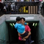 An Afghan boy kisses his brother as they exit from a metro station at Victoria square, where many stay temporarily before trying to continue their trip to more prosperous northern European countries, in Athens, Wednesday, Sept. 23, 2015. (AP Photo/Fotis Plegas G.)