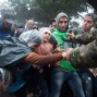 Macedonian border police helps refugees and migrants to pass in heavy rainfall from the northern Greek village of Idomeni to southern Macedonia, Thursday, Sept. 10, 2015. (AP Photo/Giannis Papanikos)