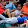 Chicago Cubs right fielder Chris Coghlan dives into the crowd to catch a foul ball hit by St. Louis Cardinals' Tommy Pham for the final out of the fifth inning of a baseball game on Wednesday, Sept. 9, 2015, in St. Louis. (AP Photo/Jeff Roberson)