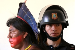 A Brazilian Pataxo man walks past a police officer during a protest against a proposed constitutional amendment that would put the demarcation of indigenous lands into the hands of the Congress, in front of the Brazilís National Congress, in Brasilia, Brazil, Tuesday, Nov. 10, 2015. A lower house commission has approved the proposal but it must make its way through the Senate, and be signed by President Dilma Rousseff to become law. (AP Photo/Eraldo Peres)
