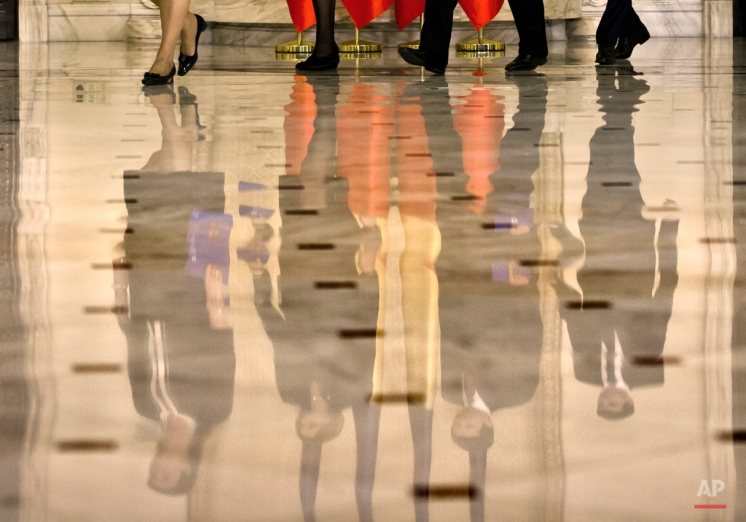 Members of Romania's new government are reflected in the floor of the hall as they arrive for the swearing in ceremony at the Cotroceni presidential palace in Bucharest, Romania, Tuesday, Nov. 17, 2015. Parliament has approved a government of technocrats headed by an ex-European Union agriculture commissioner who was designated with heading the government after the previous government collapsed amid mass protests in the wake of a nightclub fire where at least 56 died. (AP Photo/Vadim Ghirda)