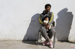 An Afghan father holds his baby at the Galatsi Olympic Hall in Athens, Wednesday, Nov. 4, 2015. The disused facility, which used during the Athens Olympics 2004, reopened a month ago for migrants as more than 600,000 people have arrived in Greece so far this year trying to head for more prosperous European Union countries in the north. (AP Photo/Thanassis Stavrakis)