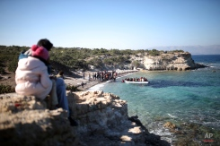 Migrants watch as others travel by dingy from the Turkish coast to the Greek island of Chios, near Cesme, Turkey, Monday, Nov. 9, 2015. Well over half a million migrants have arrived in Greece from Turkey and the vast majority don't want to stay so head north through the Balkans to other, more prosperous European Union countries.(AP Photo/Emre Tazegul)