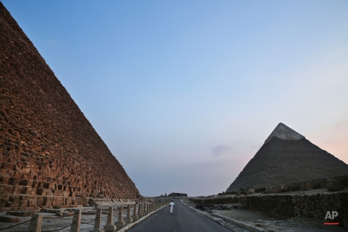 An Egyptian policeman walks past the Khufu pyramid, left, towards the Khafre pyramid, right, in Giza, Egypt, Monday, Nov. 9, 2015. Egypt's Antiquities Ministry says a scanning project in the Giza pyramids has identified thermal anomalies, including one in the largest pyramid, built by Cheops, known locally as Khufu. (AP Photo/Nariman El-Mofty)