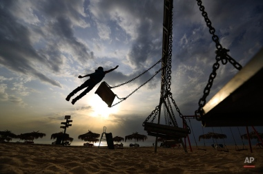 Syrian refugee boy Mohammed Assaf, 9, jumps from a swing as he plays under cloudy skies at the public beach of Ramlet al Bayda in Beirut, Lebanon, Wednesday, Nov. 4, 2015. A thick sandstorm cloaked the Middle East on Wednesday, clouding skies across the region. (AP Photo/Hassan Ammar)