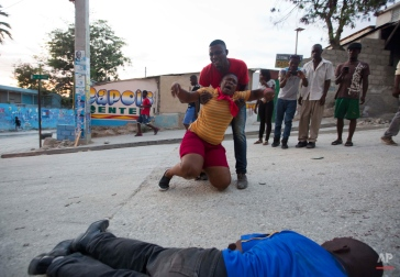 """Supporters of Presidential candidate Moise Jean-Charles react as a dead body lies on the street after official results of the elections were announced by the Provisional Electoral Council in the neighborhood of Delmas 33, Port-au-Prince, Haiti, Thursday Nov. 5, 2015. Government-backed candidate Jovenel Moise and former state construction chief Jude Celestin will advance to a runoff election for Haiti's presidency as former senator Jean-Charles placed third. Jean-Charles said the results were a sham orchestrated by outgoing President Michel Martelly and called on his supporters to participate in a """"peaceful revolution"""" to ensure their voice is heard as tire barricades were already burning in several spots of Port-au-Prince. Onlookers, also Jean-Charles supporters, said the dead man was one of them and claimed he was shot in the neck by policemen in uniform riding on a civilian car from a new police unit referred to as BOID.(AP Photo/Dieu Nalio Chery)"""