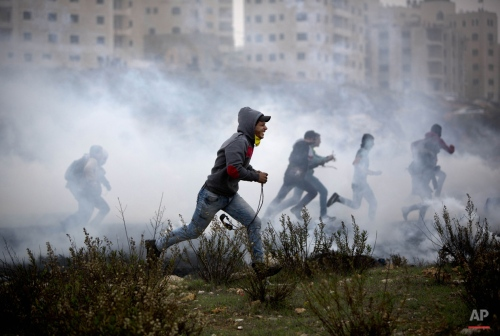Palestinian protesters run for cover from tear gas fired by Israeli soldiers during clashes, after the funerals of Ahmed Abu al-Aish, 28, and Laith Manasrah, 21, from Qalandia refugee camp, in the West Bank city of Ramallah, Monday, Nov. 16, 2015. Two Palestinians were killed and three wounded in clashes with Israeli troops early Monday in a Palestinian refugee camp in the Jerusalem area, a Palestinian health official said. (AP Photo/Majdi Mohammed)