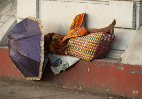 A man sleeps in the alcove of a building near the Yangon river in Myanmar, Wednesday, Nov. 4, 2015. On Sunday Myanmar will hold what is being viewed as the country's best chance for a free and credible election in a quarter of a century. (AP Photo/Mark Baker)