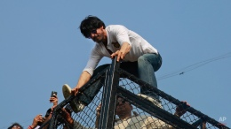 Bollywood superstar Shah Rukh Khan climbs on to the fence of his house to greet his fans who have gathered outside on his birthday in Mumbai, India, Monday, Nov. 2,2015. (AP Photo/Rafiq Maqbool)