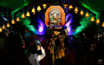 An Indian devotee takes photos of a portrait of Hindu goddess Kali as others stand inside the worship place on Kali Puja, in Kolkata, India, Tuesday, Nov. 10, 2015. The festival is dedicated to the worship of goddess Kali. (AP Photo/Bikas Das)