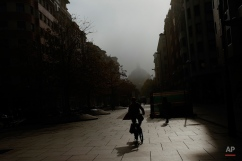 A cyclist rides her bicycle as fog covers the city on an autumn morning in Pamplona, northern Spain, Monday, Nov. 9, 2015. (AP Photo/Alvaro Barrientos)