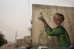 """A mural on a wall with Arabic reads """"what will I be when I grow up?"""" stands amid a sandstorm in Amman, Jordan, Wednesday, Nov. 4, 2015. A thick sandstorm cloaked parts of the Middle East on Wednesday, clouding skies and disrupting travel for the U.S. first lady, while flooding in Egypt killed three people. (AP Photo/Nasser Nasser)"""