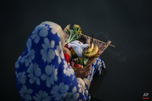 A Hindu woman performs rituals to mark Chhath Puja festival in Hyderabad, India, Tuesday, Nov. 17, 2015.During Chhath, an ancient Hindu festival, rituals are performed to thank the Sun god for sustaining life on earth. (AP Photo/Mahesh Kumar A.)