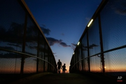 Two men are silhouetted as they walk along the overpass above the Pacific Coast Highway near the Santa Monica Pier, Wednesday, Nov. 4, 2015, in Santa Monica, Calif. Showers and isolated thunderstorms popped up Wednesday across the lower elevations of southern California. (AP Photo/Jae C. Hong)