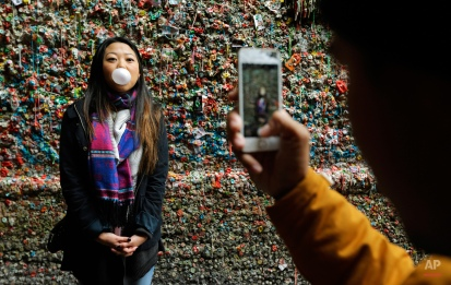 """Jessica Wang, left, visiting from Los Angeles, has her photo taken by Michael Teylan, right, at Seattle's """"gum wall"""" at Pike Place Market, Monday, Nov. 9, 2015. On Tuesday, a steam-cleaning process to remove all of the gum from the walls is scheduled to begin, the first full cleaning the quirky tourist attraction has received in 20 years. (AP Photo/Ted S. Warren)"""