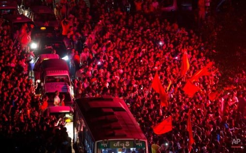 Traffic attempts to make it's way through supporters of Myanmar's National League for Democracy party as they wait for election results to be posted outside the NLD headquarters in Yangon, Myanmar, Monday, Nov. 9, 2015. With tremendous excitement and hope, millions of citizens voted Sunday, Nov. 8 in Myanmar's historic general election that will test whether the military's long-standing grip on power can be loosened, with opposition leader Aung San Suu Kyi's party expected to secure an easy victory. (AP Photo/Mark Baker)