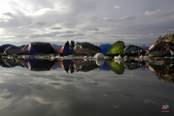 Tents are reflected in a puddle with waste inside the camp known as the Jungle in Calais, northern France, Tuesday, Nov. 3, 2015. More than 5000 migrants are fleeing conflict zones or poverty at the rapidly growing camp outside Calais. All hope to make it across the English Channel to Britain. (AP Photo/Markus Schreiber)