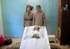 Maria Ion, a 38 year-old widow, mother of five, who died in last Friday's fire at the Colective nightclub where she occasionally worked as a cleaning lady, lies in a coffin wearing a bride dress as two of her children, Denisa, 15 years-old, left, and her 11 year-old sister Alexandra pose next to it after requesting a souvenir picture with their mother, at the family house in Bucharest, Romania, Tuesday, Nov. 3, 2015. Maria Ion, who struggled on a very small income is survived by five children, a victim of a fire that engulfed a nightclub killing tens of people and injured many others was buried Tuesday in Bucharest. (AP Photo/Vadim Ghirda)