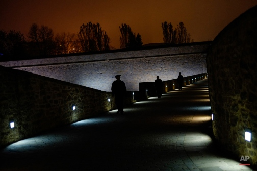 A man wearing a basque beret goes for a walk alongs an ancient stretch of wall of the old city, as the autumn darkness falls, in Pamplona, northern Spain, Tuesday, Nov. 10, 2015. (AP Photo/Alvaro Barrientos)