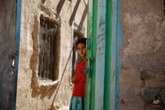 A girl stands in a doorway as she watches children receiving a polio vaccination, during a house-to-house polio immunization campaign in Sanaa, Yemen. Monday, Nov. 9, 2015. A national three-day anti-Polio immunization campaign to vaccinate more than 5 million children across Yemen began on Monday. (AP Photo/Hani Mohammed)