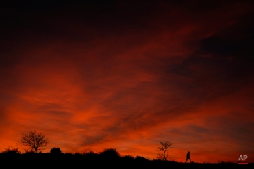 Silhouettes of trees and a woman, contrast on a fire-red sunset, as the autumn darkness falls outside of Pamplona, northern Spain, Tuesday, Nov. 17, 2015. (AP Photo/Alvaro Barrientos)