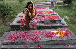 A Pakistani Christian woman lays rose petals on a grave of her family member on All Soulsí Day in Lahore, Pakistan, Monday, Nov. 2, 2015. The day honors the dead as friends and families gather in cemeteries to decorate graves of loved ones with candles and flowers and offer prayers. (AP Photo/K.M. Chaudary)