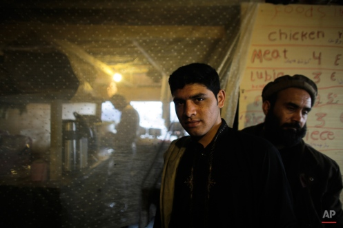 Migrants stand next to a kitchen of a makeshift Afghan restaurant inside the camp known as the Jungle in Calais, northern France, Tuesday, Nov. 3, 2015. More than 5000 migrants are fleeing conflict zones or poverty at the rapidly growing camp outside Calais. All hope to make it across the English Channel to Britain. (AP Photo/Markus Schreiber)