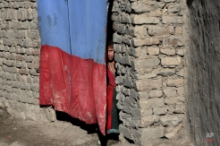 An Afghan refugee girl peers through the curtain of her temporary home on the outskirts of Kabul, Afghanistan, Tuesday, Nov. 17, 2015. (AP Photo/Rahmat Gul)