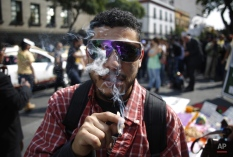 A supporter of the legalization of marijuana smokes outside the Supreme Court in Mexico City, Wednesday, Nov. 4, 2015. Mexico's court ruled Wednesday that growing, possessing and smoking marijuana for recreation are legal under a person's right to personal freedoms. (AP Photo/Eduardo Verdugo)