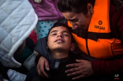 An exhausted boy is helped by his mother at a beach, after their arrival on a dinghy from the Turkish coast on the northeastern Greek island of Lesbos Tuesday, Nov. 17, 2015. Greek authorities say at least nine people, including four children, have died in the eastern Aegean Sea when a plastic boat carrying refugees or economic migrants overturned near the island of Kos. (AP Photo/Santi Palacios)