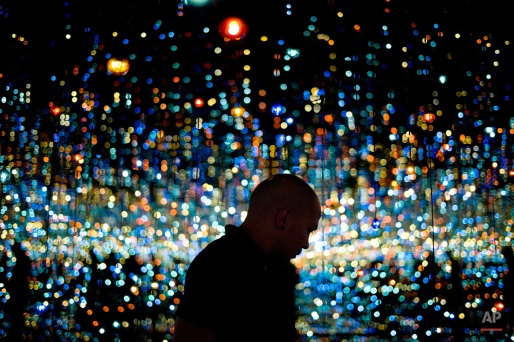 Redan Magbanua views Yayoi Kusama's Infinity Mirrored Room at the Broad museum, Tuesday, Nov. 10, 2015, in downtown Los Angeles. The contemporary art museum founded by philanthropist Eli Broad opened September. (AP Photo/Jae C. Hong)