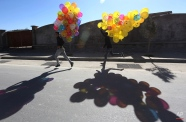 Afghan boys run as they hope to sell colored balloons on a street in Kabul, Afghanistan, Monday, Nov. 16, 2015. (AP Photo/Rahmat Gul)