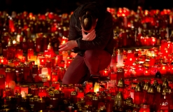 A man touches his forehead holding a candle outside the Colectiv nightclub in Bucharest, Romania, Friday, Nov. 6, 2015, as people mark one week since a deadly fire started during a concert. Romanian prosecutors on Friday questioned an owner of the nightclub where a fire killed 32 people and injured 180. (AP Photo/Vadim Ghirda)