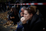 A woman prays as they pay their respect in front of a floral tribute near the Bataclan concert hall after the terrorist attacks in Paris, Monday, Nov. 16, 2015. France is urging its European partners to move swiftly to boost intelligence sharing, fight arms trafficking and terror financing, and strengthen border security in the wake of the Paris attacks. (AP Photo/Daniel Ochoa de Olza)
