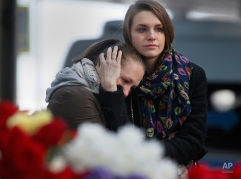 Young women grieve at an entrance of Pulkovo airport outside St.Petersburg, Russia, on Monday, Nov. 2, 2015. In a massive outpouring of grief, thousands of people flocked to St. Petersburg's airport, laying flowers, soft toys and paper planes next to the pictures of the victims of the crash of a passenger jet in Egypt that killed all 224 on board in Russia's deadliest air crash to date.(AP Photo/Dmitry Lovetsky)