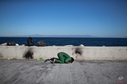 An Iraqi man prays at the port of Mytilene on the island of Lesbos, Greece, Monday, Nov. 2, 2015. More than 300,000 people have traveled on dinghies and boats from nearby Turkey to Lesbos this year, with dozens dying along the way. (AP Photo/Marko Drobnjakovic)