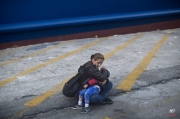 A woman holds a child as they wait to board a ferry at the port of Mytilene on the island of Lesbos, Greece, Friday, Nov. 6, 2015. Thousands of migrants and refugees were allowed to board vessels in Mytilene on Friday, as Greek ferries ended a strike that had left them trapped on eastern Aegean islands. (AP Photo/Marko Drobnjakovic)