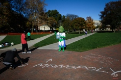 """Buddie, the mascot for the pro-marijuana legalization group ResponsibleOhio, stands in front of an opposition voter's chalk lettering that reads """"monopoly"""" at the Ohio State University oval on election day, Tuesday, Nov. 3, 2015, in Columbus, Ohio. Ohio voters headed to the polls today to decide whether to allow marijuana to be grown, processed and consumed within the state's borders. (AP Photo/John Minchillo)"""